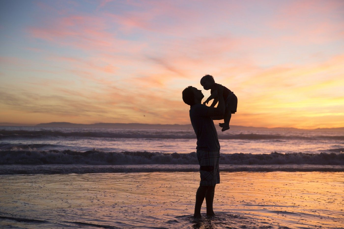 father holding a child up while the sun is setting while standing in the ocean beach